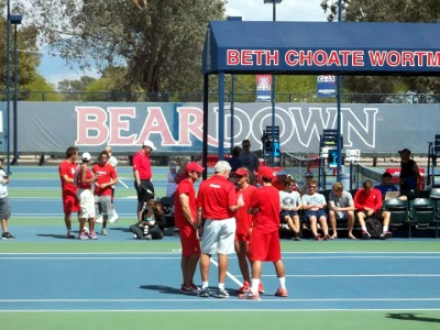 Tennis players in red in a huddle