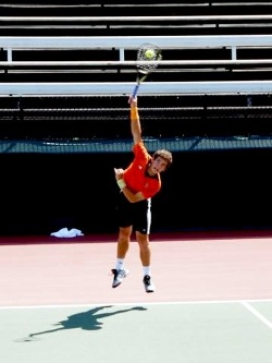 Male tennis player playing a forehand smash