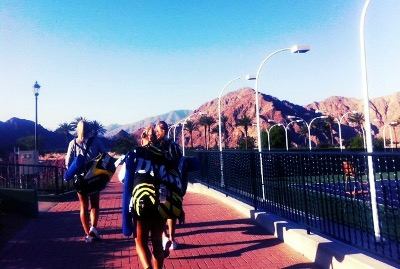 Tennis players walking away with hills in the background